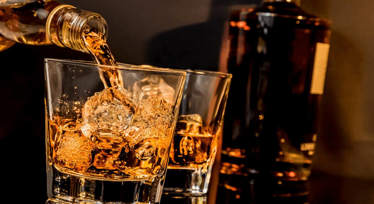 Whiskey in zwei Gläsern mit Eiswürfel fuellen mit Flasche im Hintergrund